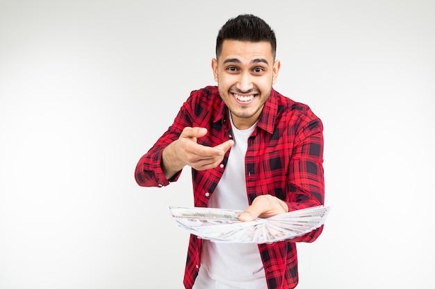 Glimlachende mens in een plaidoverhemd dat een bos van geld op een witte achtergrond standhoudt
