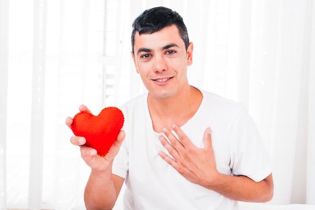 Glimlachende mens met hand op borst die decoratief hart houdt