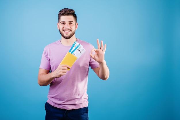 Glimlachende mens met vliegtuigtickets en paspoort dat over blauw wordt geïsoleerd