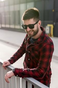 Glimlachende mens met zonnebril die op omheining leunt