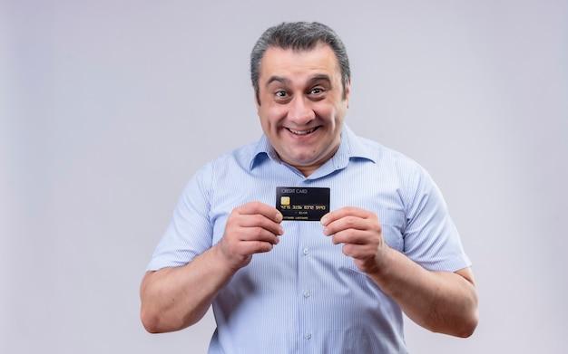 Glimlachende mens op middelbare leeftijd die blauw verticaal gestript overhemd draagt dat creditcard op een witte achtergrond toont