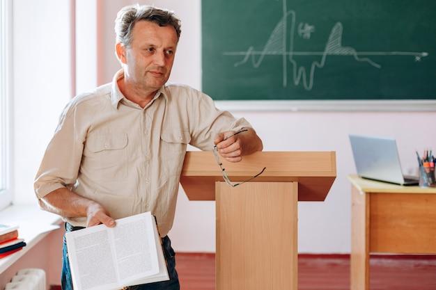 Glimlachende midden oude leraar die een boek houdt dat zich en aan tribune bevindt leunt.