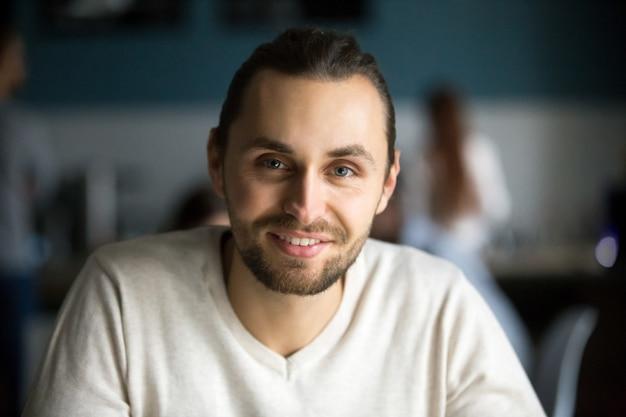 Glimlachende millennial mens die camera in koffie, headshot portret bekijkt