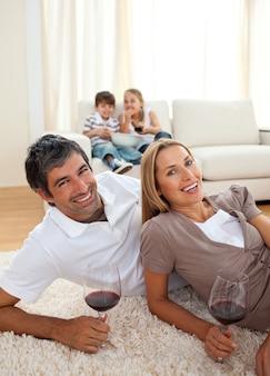 Glimlachende minnaars die wijn drinken die op de vloer liggen