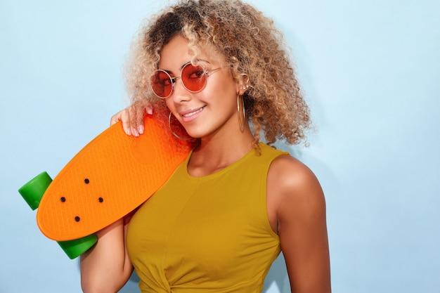 Glimlachende modelvrouw in trendy de zomer korte jeans en zonnebril die met met een skateboard rijden stellen