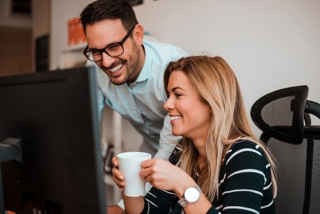 Glimlachende moderne bedrijfsmensen die aan bureaucomputer werken. een pauze nemen.