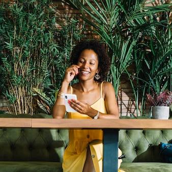 Glimlachende modieuze jonge vrouw die mobiele telefoon in het restaurant bekijkt