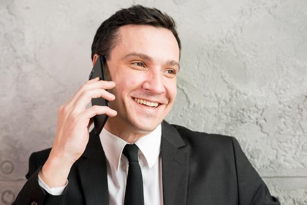 Glimlachende modieuze zakenman die op telefoon spreekt