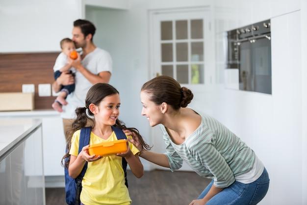 Glimlachende moeder die aan dochter spreekt
