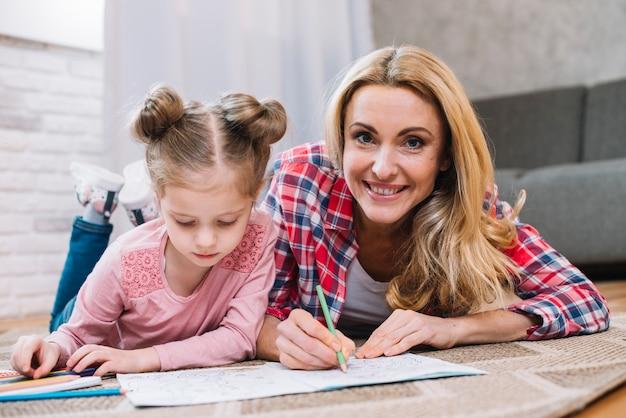 Glimlachende moeder die aan haar dochter in tekening bijstaan die op tapijt liggen