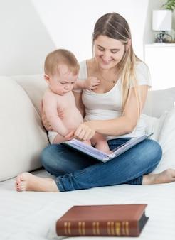 Glimlachende moeder die afbeeldingen in een oud boek laat zien aan haar 9 maanden oude babyjongen