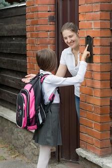 Glimlachende moeder die de deur opent voor haar dochter die van school kwam