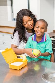 Glimlachende moeder die de lunch van de zoonsschool voorbereidt