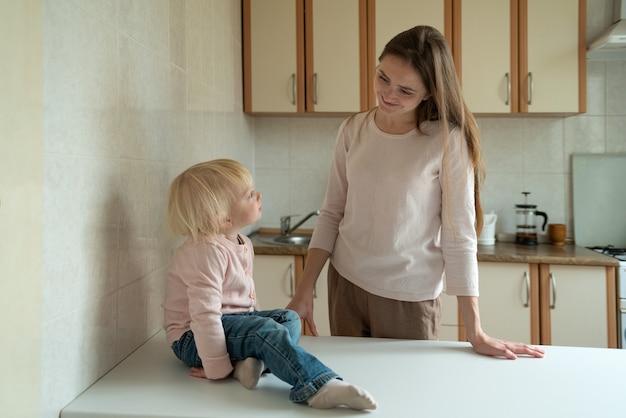 Glimlachende moeder die dochtertje aan tafel in de keuken bekijkt