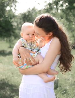 Glimlachende moeder die haar dochtertje in de armen houdt, praat, baby kijkt met liefde en aanbidding