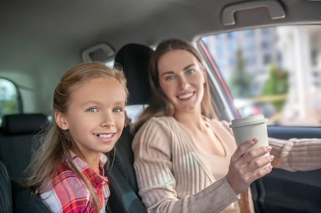 Glimlachende moeder die koffiekop houdt, die in auto met haar dochter zit
