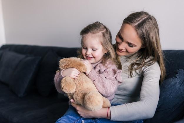 Glimlachende moeder die leuk de teddybeerstuk speelgoed koesteren die van de meisjeholding liefde en zorg in familie tonen