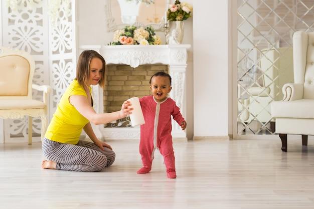 Glimlachende moeder die thuis speelt met zoontje van gemengd ras
