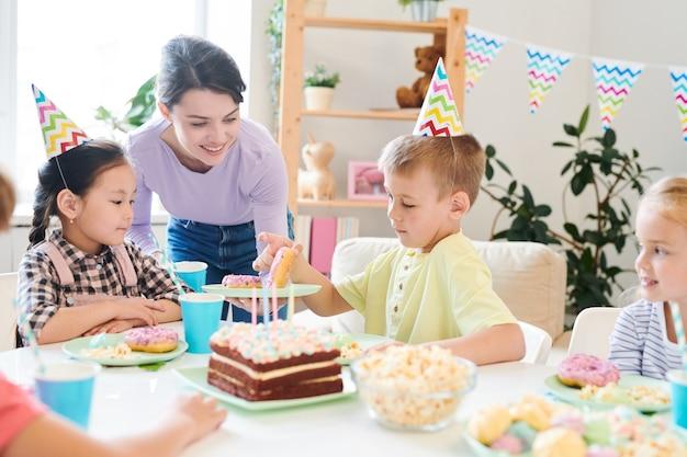 Glimlachende moeder die verse zelfgemaakte donuts aanbiedt aan groep kleine vrienden aan tafel tijdens verjaardagsfeestje thuis