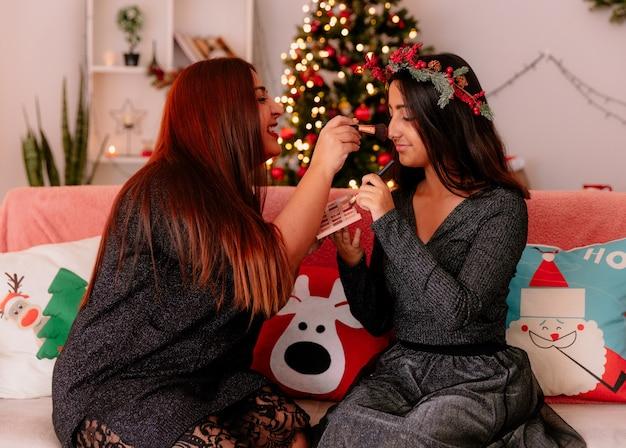 Glimlachende moeder doet make-up aan haar dochter zittend op de bank genieten van kersttijd thuis