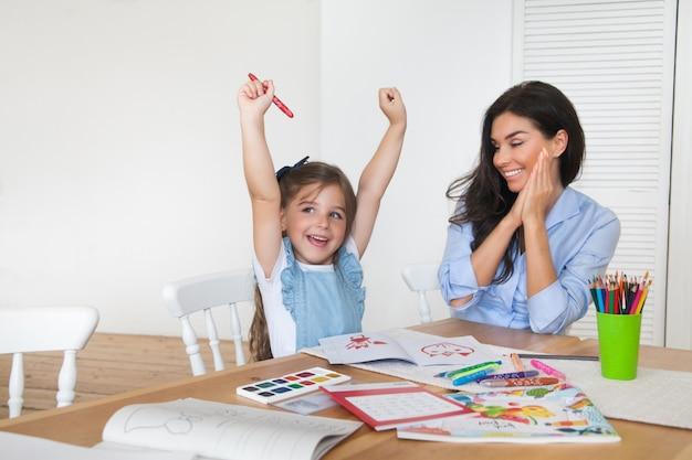 Glimlachende moeder en dochter bereiden zich voor op school en houden zich bezig met tekenen met potloden en verven