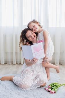 Glimlachende moeder en dochter de dagkaart van de lezingsmoeder samen thuis