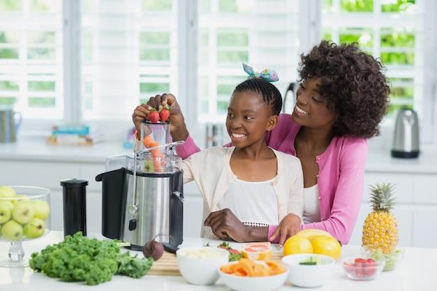 Glimlachende moeder en dochter die aardbei smoothie in keuken voorbereiden