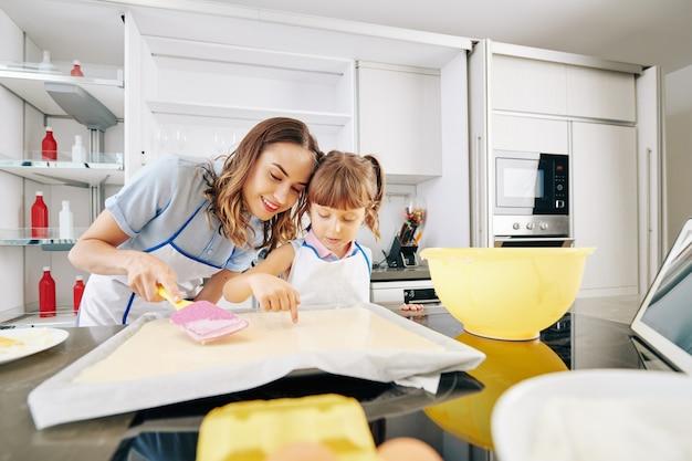 Glimlachende moeder en dochter die controleren of er geen bellen in vloeibaar deeg op bakselblad zitten