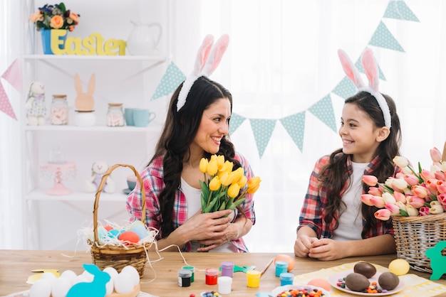 Glimlachende moeder en dochter die de pasen-dag thuis vieren