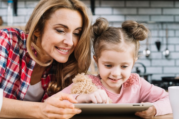 Glimlachende moeder en dochter die digitale tablet in keuken gebruiken