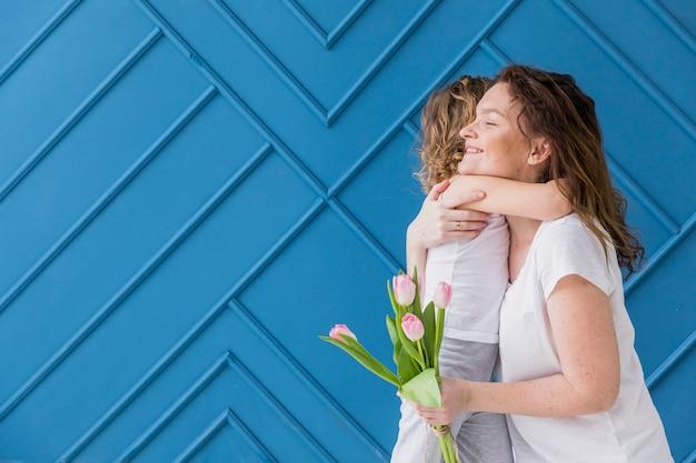 Glimlachende moeder en dochter die elkaar koesteren die tulpenbloemen houden tegen blauwe achtergrond