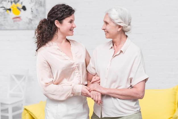 Glimlachende moeder en dochter die elkaars hand thuis houden