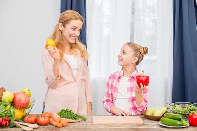 Glimlachende moeder en dochter die gele citroen en rode groene paprika in hand houden