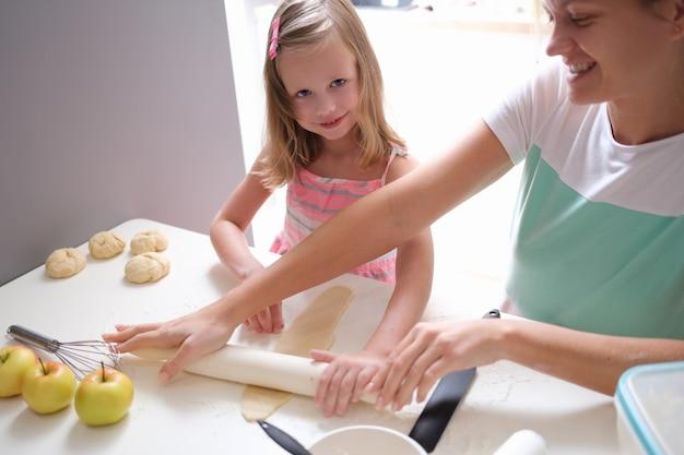 Glimlachende moeder en dochter rollen deeg uit met deegroller. samen zoet eten koken met kinderconcept
