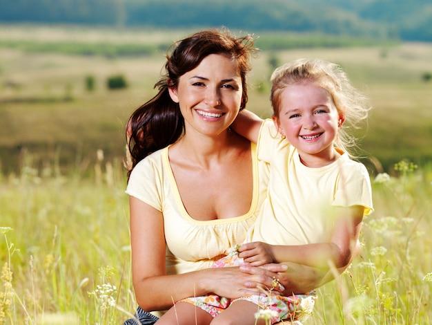 Glimlachende moeder en dochtertje van aard.