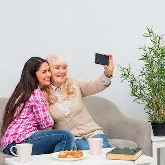 Glimlachende moeder en haar jonge dochter die selfie op celtelefoon thuis nemen