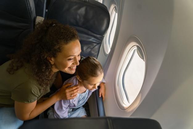 Glimlachende moeder en haar kind kijken naar het landschap buiten het vliegtuigraam