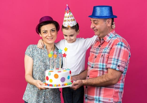Glimlachende moeder en vader met feestmutsen die verjaardagstaart samen houden met hun zoon geïsoleerd op roze muur met kopieerruimte