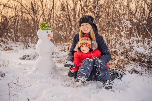 Glimlachende moeder en zoon die een sneeuwman buiten maken