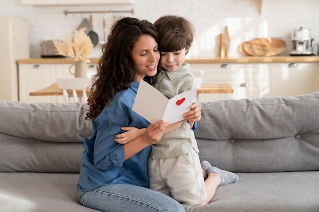 Glimlachende moeder houdt een ansichtkaart vast op gelukkige moederdag of verjaardag, lees de groeten van de peuterzoon