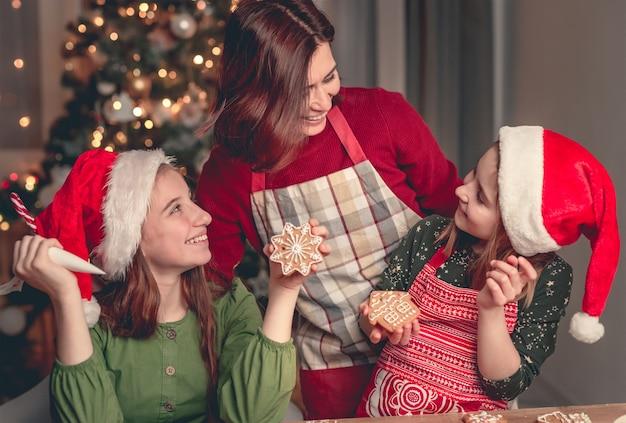 Glimlachende moeder met dochters die thuis peperkoek bakken bij de kerstboom