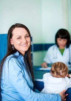 Glimlachende moeder met haar kind bij artsenbureau
