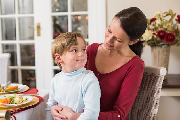 Glimlachende moeder met haar zoon die op overlapping zit