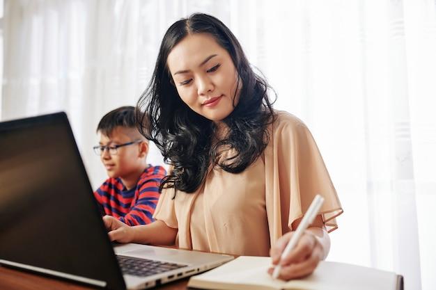 Glimlachende moeder webinar op laptop kijken en schrijven in notitieblok wanneer haar zoon aan tafel in de buurt speelt