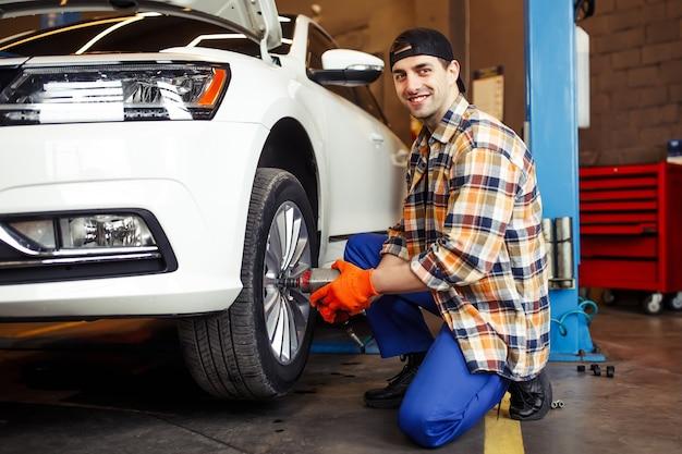 Glimlachende monteur die het wiel op de auto verandert met een pneumatische moersleutel en naar de voorkant kijkt