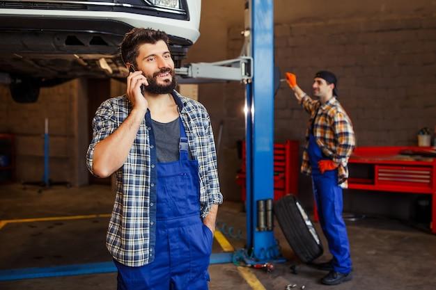 Glimlachende monteur praten op de smartphone met opgeheven auto en collega achter