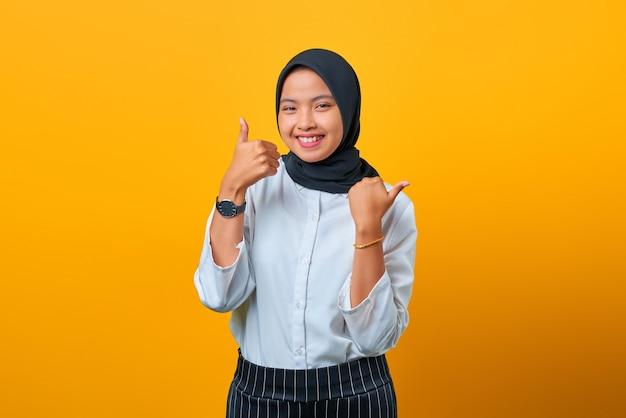 Glimlachende mooie aziatische vrouw die duim omhoog maakt geïsoleerd over gele achtergrond