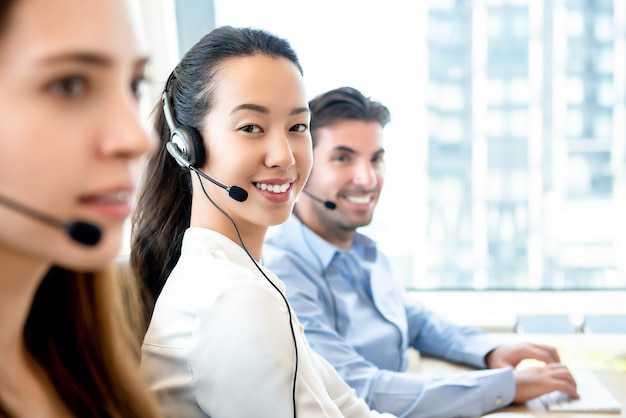 Glimlachende mooie aziatische vrouw die in call centre werkt
