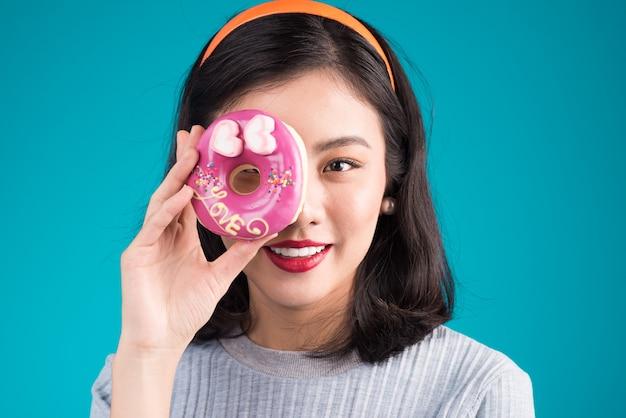 Glimlachende mooie aziatische vrouw gekleed in pin-up stijl jurk met donut over blauw.