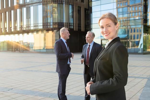 Glimlachende mooie bedrijfsvrouw die bureaukostuum draagt, die zich buiten bevindt en camera bekijkt. pratende zakenmensen en stadsgebouwen op de achtergrond. kopieer ruimte. vrouwelijk portret concept